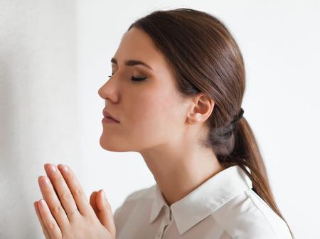 worship god: Closeup portrait of a young woman praying