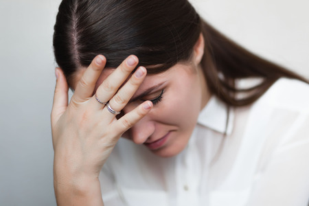 Beautiful and sad young woman in Headache or problems, hand at her forehead. photo