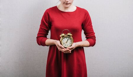 Woman hands holding an alarm clock On a gray background.