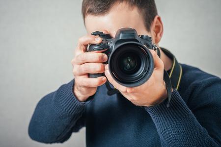 Man photographs on digital camera. On a gray background.