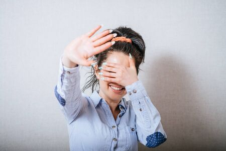 woman stop: Woman showing a stop, eyes with her hand closed. On a gray background. Stock Photo