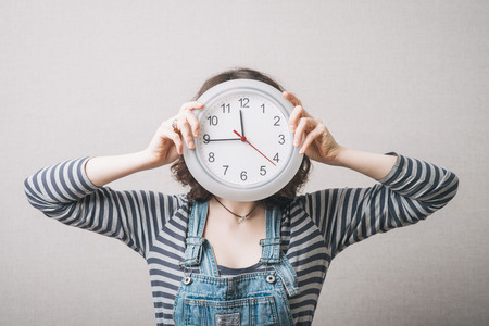ageing: Woman holding a clock instead of a head. Gray background Stock Photo