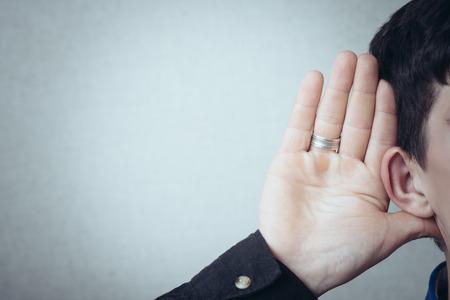oir: Un hombre con su mano cerca de su oído. Gesto no puede oír sin escuchar, hablar más fuerte. Sobre un fondo gris Foto de archivo
