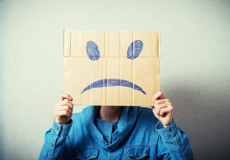 masquerader: Curly man with a kraft cardboard instead of a head, a sad smiley. On a gray background.