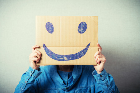 hiding face: Curly man with a kraft cardboard instead of a head, a cheerful smiley. On a gray background. Stock Photo