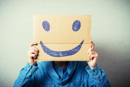 cara sonriente: Hombre rizada con un cart�n kraft en lugar de una cabeza, un smiley alegre. Sobre un fondo gris. Foto de archivo