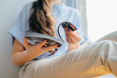 Attractive girl reading magazine on  window. girl holding magazine at home 스톡 콘텐츠