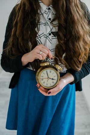 Jonge vrouw met alarmclock in de ochtend