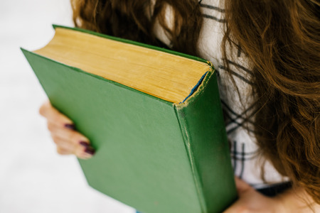 two page spread: A woman(female) two hands hold a book(note, diary) spread(unfold)