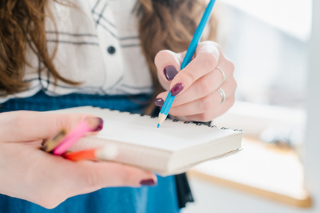 blank page: Close-up of a female hand writing on an blank notebook with a blue pen.
