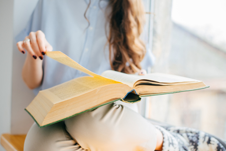 autodidact: Image of the book in womans hands near the window