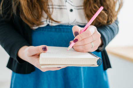 Womans hand using a pink pencil noting on notepad