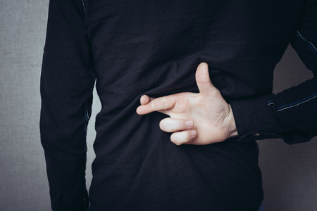 Male hands behind his back, fingers crossed. Luck, the desire to think. Gesture. On a gray background.