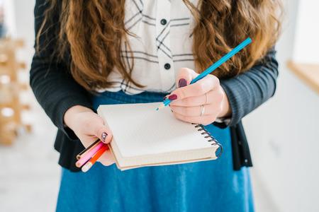 hacer: Primer plano de una mano escribiendo femenina en un cuaderno en blanco con una pluma azul.