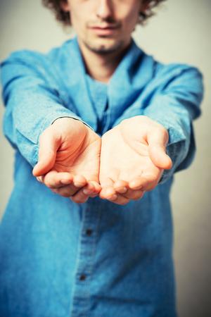 manos abiertas: Joven rizada muestra la palma vacía. Sobre un fondo gris