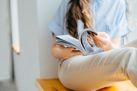 home and leasure concept - smiling woman reading magazine at home near the window Stock Photo