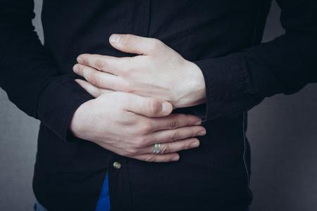 Man hands on his stomach, stomach ache. Gesture stomach ache, cramps. On a gray background Standard-Bild