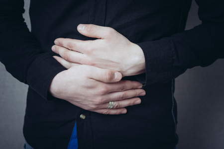 Man hands on his stomach, stomach ache. Gesture stomach ache, cramps. On a gray background Stockfoto