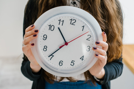 timekeeping: Confident Friendly Young Caucasian  Woman Holding A Large Clock In Hands Showing The Success And Joy Of Good Office Timekeeping In A Happy Hour Concept