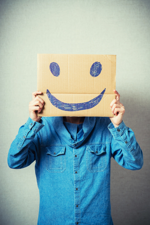 masquerader: Curly man with a kraft cardboard instead of a head, a cheerful smiley. On a gray background. Stock Photo