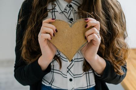 mignonne petite fille: Une jeune femme tient un coeur de papier de construction couper près de la fenêtre.