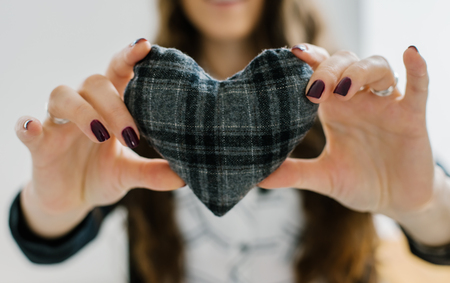heart hands: Picture of a small gray heart in hands, female holds handmade sewn soft toy, woman with Valentine gift against the window, happy girl smiling, conceptual image of health care or love.