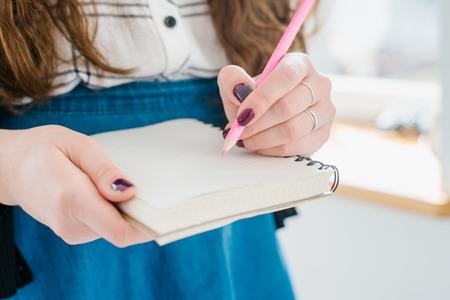 hacer: Mano de la mujer con un lápiz de color rosa señalando la hoja de notas Foto de archivo