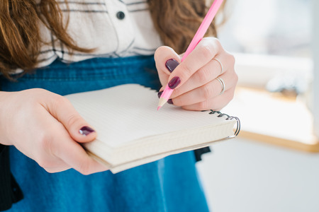 noting: Womans hand using a pink pencil noting on notepad