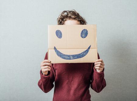 masquerader: man holding the sad smiley