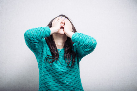 screaming face: Pretty girl in hysterics covers her face Stock Photo