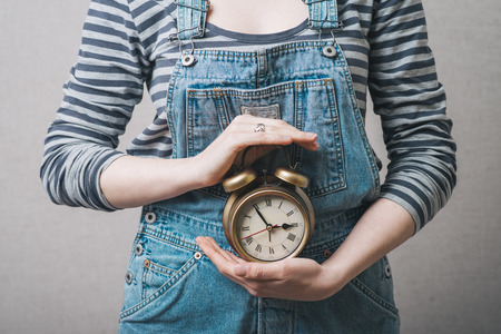 Mooie vrouw met wekker in de hand, gekleed in een pak Stockfoto - 42333497