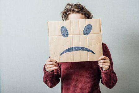 homme triste: homme tenant le smiley triste Banque d'images