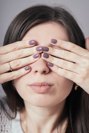 peek a boo: girl closes eyes with her hands Stock Photo