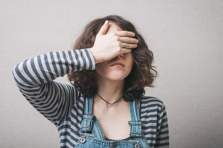 one eye: girl covering her eyes with her hands