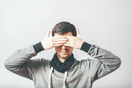 closes eyes: man closes eyes with her hands Stock Photo