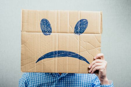 sad face: man holding the sad smiley