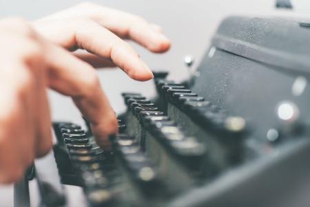 handsome journalist writing with typewriter Reklamní fotografie