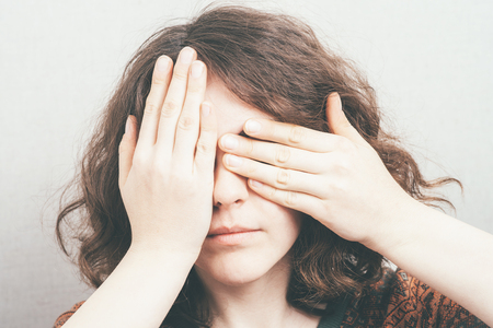 impaired: girl closes eyes with her hands Stock Photo