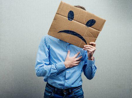 expressing: man holding the sad smiley