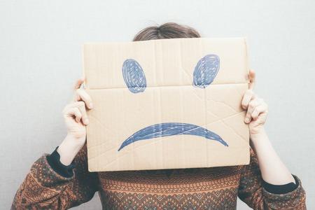 are hidden: Girl shows a sad smiley Stock Photo