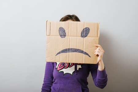 Girl with cardboard sad smiley 免版税图像
