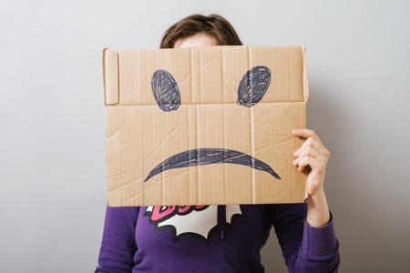 sad smiley: Girl with cardboard sad smiley Stock Photo