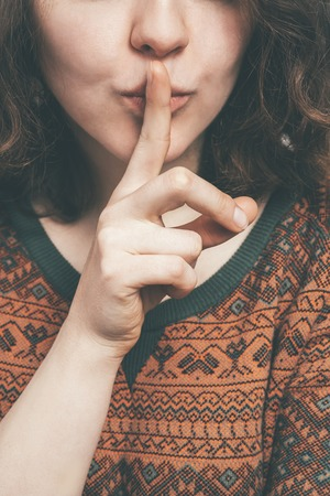 silently: woman, put a finger to his lips silently