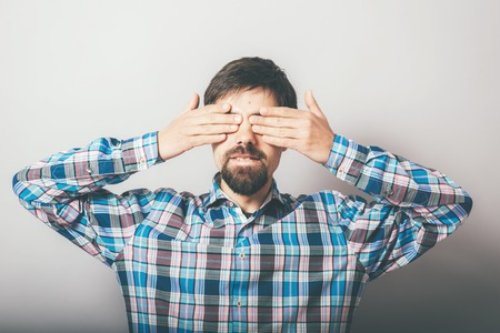closes eyes: bearded man closes eyes with her hands Stock Photo