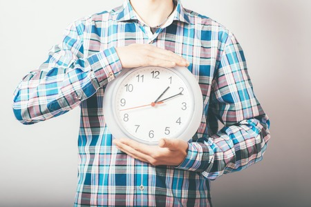 Businessman holding large clock