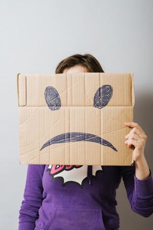 boxy: Girl with cardboard sad smiley Stock Photo
