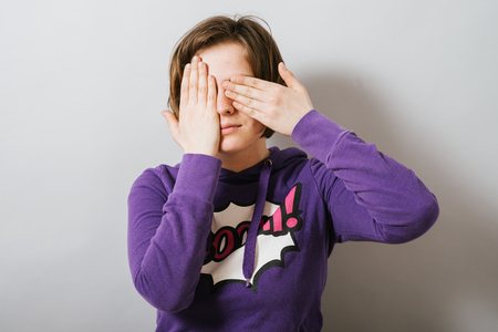 closes eyes: girl closes eyes with her hands Stock Photo