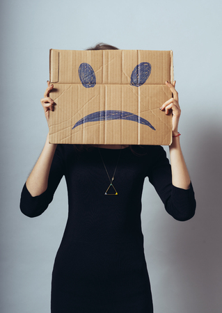woeful: Young woman standing with a cardboard on his head with sad face