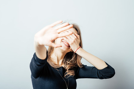 young woman laughing covering his face