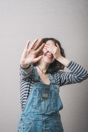 Happy girl shows five fingers, and covers his face